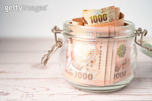 Thai baht banknotes in grass jar on wooden background, business saving finance investment concept.