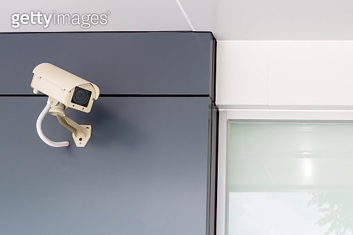 Security CCTV camera surveillance system outdoor of house. A blurred night city scape background. Modern CCTV camera on a wall. Equipment system service for safety life or asset.