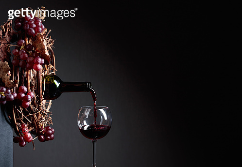 Red wine pouring from a bottle into a glass.