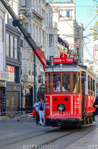 Red retro tram rides along the busy Istiklal street in Istanbul