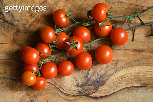 Fresh tomatoes on wood background. Closeup of fresh tomatoes on olive tree wooden background.