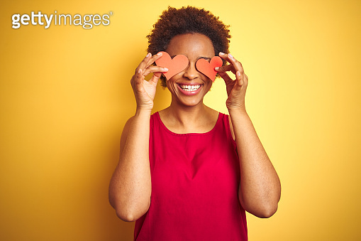 African american woman holding romantic paper hearts over yellow isolated background with a happy face standing and smiling with a confident smile showing teeth