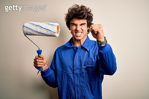 Young handsome painter man holding roller wearing uniform over isolated white background annoyed and frustrated shouting with anger, crazy and yelling with raised hand, anger concept