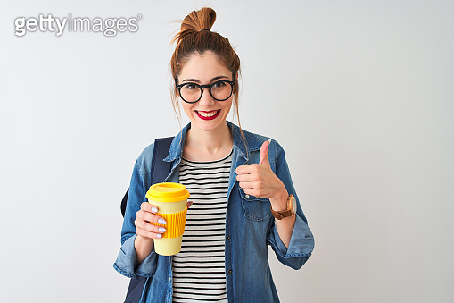 Beautiful redhead student woman drinking take away coffee over isolated white background happy with big smile doing ok sign, thumb up with fingers, excellent sign