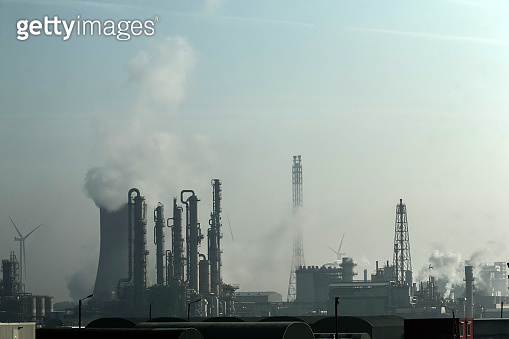 A factory with an horizon full of chimneys releasing steam