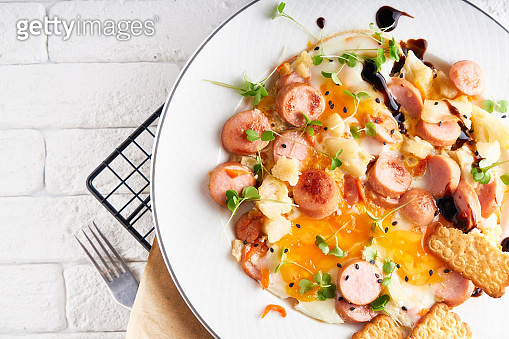 Healthy homemade breakfast. eggs with sausages , spices ,arugula served in a plate