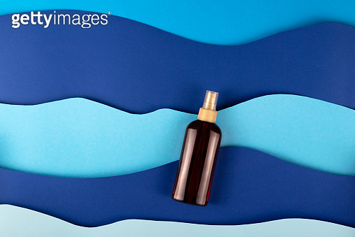 Blue background paper art sea waves with sunscreen for skin care.