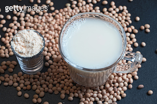 soyabeans milk with raw soyabeans and powder in the background