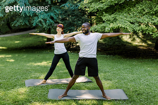 Multiethnic young man and woman synchronously practice yoga outdoors in the park, standing on yoga mats with arms and legs outstretched, in a warrior's asana, meditating and balancing
