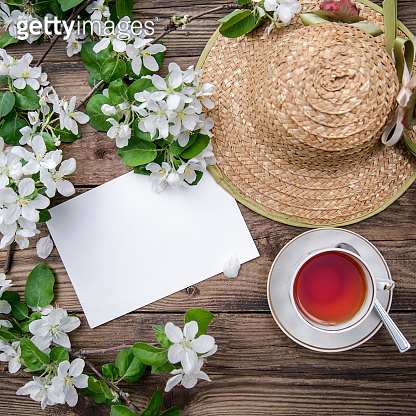 Spring layout with branches of a flowering apple tree, a cup of tea and a straw hat