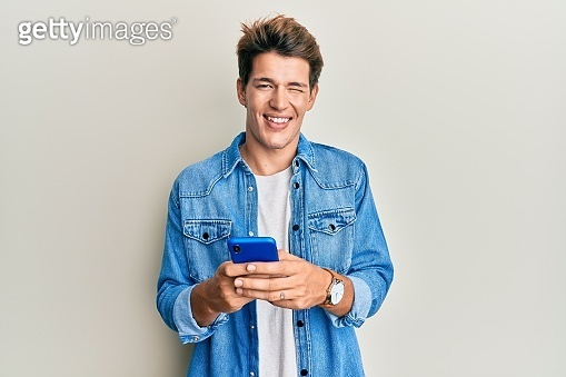 Handsome caucasian man using smartphone winking looking at the camera with sexy expression, cheerful and happy face.