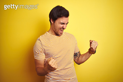 Young handsome man with tattoo wearing striped t-shirt over isolated yellow background very happy and excited doing winner gesture with arms raised, smiling and screaming for success. Celebration concept.