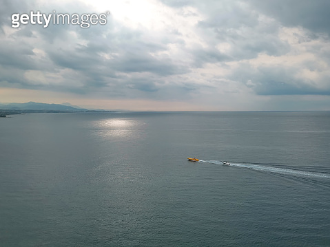 Yellow rescue boat tows a small motor boat along the seashore on an early cloudy morning