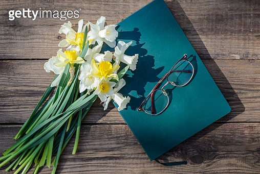White and yellow daffodils, book and glasses on a wooden background