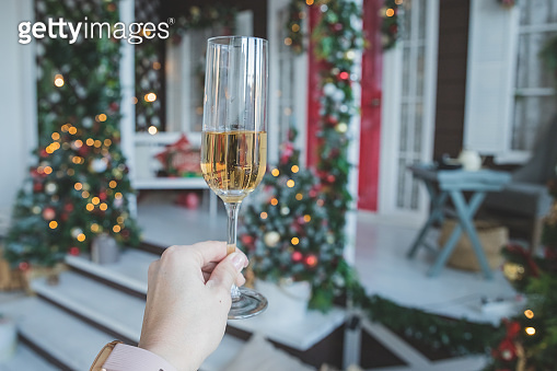 toast with glass of champagne in female hand.New Years Eve celebration.party, drinks, holidays, people and celebration concept.Champagne and new year decoration.Party with sparkling wine