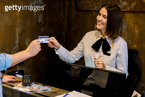 Female receptionist at the hotel reception. Cropped image of young man giving credit card to receptionist at counter in hotel