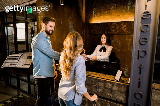 Female receptionist and young couple in hotel. Happy Couple, Caucasian man and woman, Checking In At Hotel Reception showing their passports