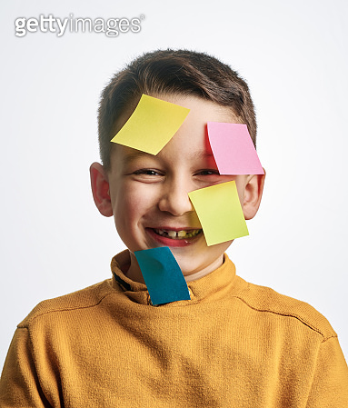 Cute child on white background. There is adhesive notes on his face.