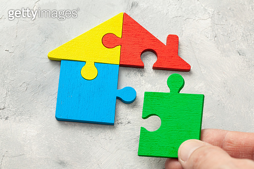 House puzzle Home loan. Parts of the house are brought together. Male hand holding puzzle piece