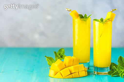 Refreshing summer cocktails made of mango, cold drink or a drink with ice on a blue gray background. Fresh summer ice cold mango cocktail or juice with mint and mango fruit