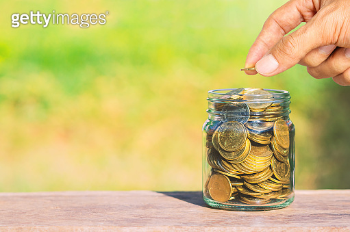 business man hand put golden coin stack growth up isolated on green blur nature background. money saving, financial growing, business startup, economy budget and investment concept.