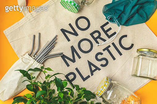 Zero waste concept. Cotton bag, bamboo cutlery, glass jar,  and straws on yellow background, flat lay,  no more plastic text , copy space