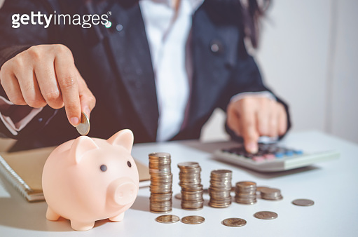 Closeup image businesswoman holding coins putting into piggy bank and calculating. concept saving money wealth for finance accounting.