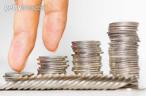 business man hand put finger walking on coin stack growth up isolated on white background. money saving, financial growing, business startup, economy budget and investment concept.