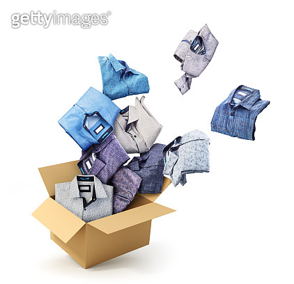 Shirts fly out from a cardboard box isolated on a white background. Donation.