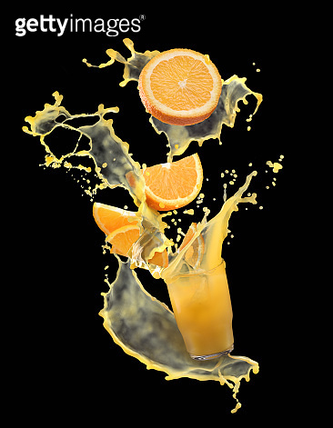 Beautiful splash of orange juice with oranges. Orange juice on a black background