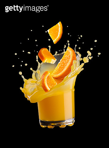 splash of orange juice in a glass on a black background