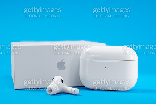New unpacked wireless headphones Apple AirPods Pro with rechargeable case and box on blue background, copy space for advertising text.