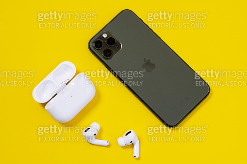Smartphone Apple iPhone 11 Pro of Midnight Green color and wireless headphones with opened charging case for active lifestyle on yellow background, top view, copy space
