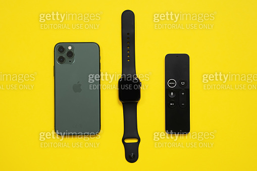 May 01, 2020, Rostov, Russia: Mobile phone iPhone 11 Pro of midnight green color, futuristic touch swipe-to-select remote control for television, and Apple Watch S4 on yellow background, top view, copy space.