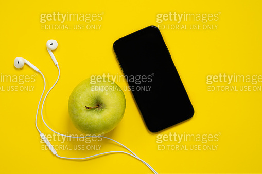 Smartphone and wired headset with green ripe apple on yellow background, top view, copy space for advertising banner of modern stylish accessories for luxury lifestyle.