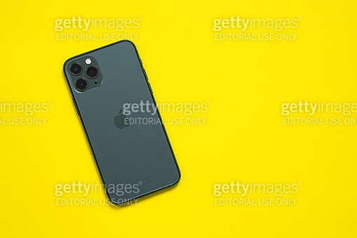 top view new midnight green Apple iPhone 11 Pro on a yellow background. The latest model of Apple mobile phones. Modern technologies.