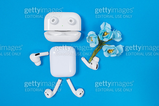 Funny man with arms, legs and eyes made of Apple wireless headphones and charging opened case like mouth of AirPods with artificial flowers in hand on blue background