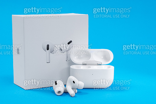 New unpacked wireless headphones Apple AirPods Pro with opened rechargeable case and box on blue background, copy space for advertising text.