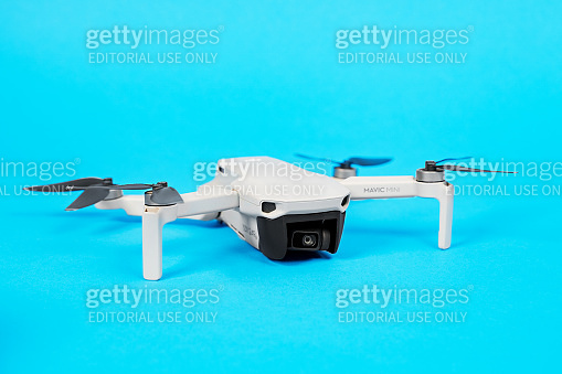 June 05, 2020, Rostov, Russia: Modern drone quadcopter DJI Mavic mini with open propeller blades with a camera isolated on blue background.
