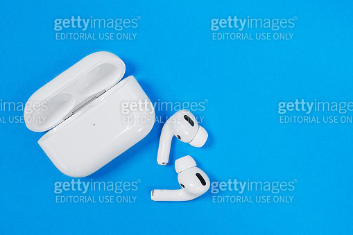 Wireless headphones Apple AirPods Pro in opened charging case with active noise cancellation immersive sound, on blue background, copy space.