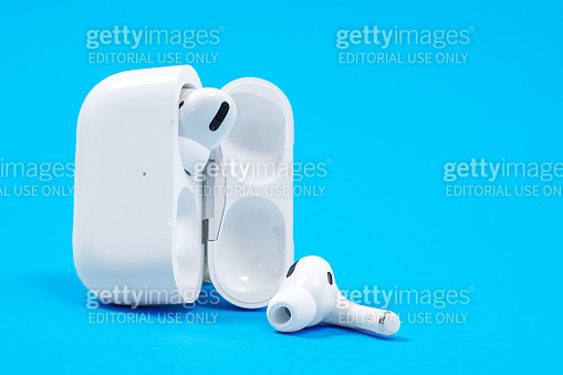 Rostov, Russia - July 06, 2020: Wireless headphones Apple AirPods Pro in opened charging case with active noise cancellation immersive sound, on blue background, copy space