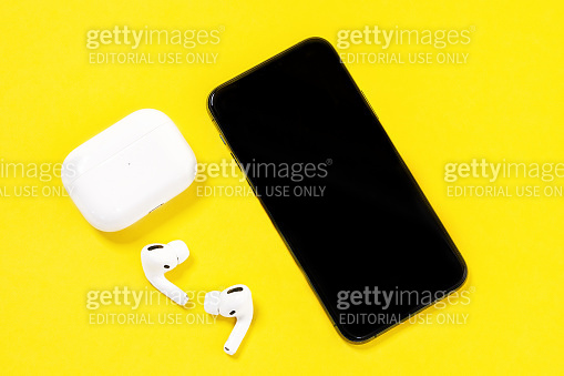 Smartphone Apple iPhone 11 Pro and wireless headphones with charging case for active lifestyle on yellow background, top view, copy space.