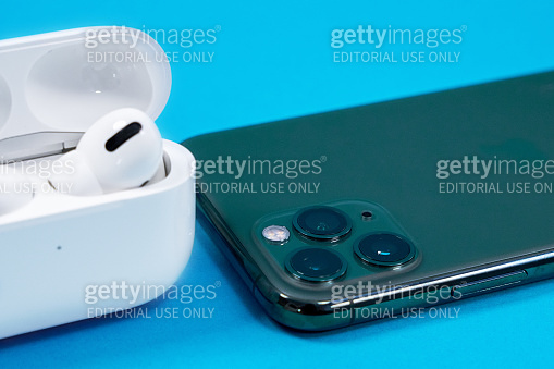 Smartphone Apple iPhone 11 Pro of Midnight Green color and wireless headphones with opened charging case for active lifestyle on blue background, top view, copy space.