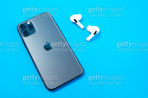 Smartphone Apple iPhone 11 Pro of Space gray color and wireless headphones with opened charging case for active lifestyle on blue background, top view, copy space.