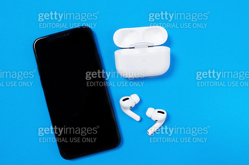 Smartphone Apple iPhone 11 Pro and wireless headphones with opened charging case for active lifestyle on blue background, top view, copy space.