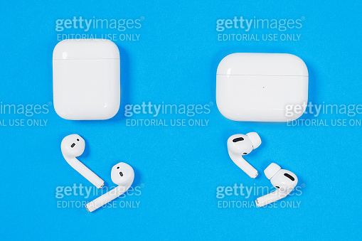 Comparison of two generations of headsets for smartphones Apple wireless rechargeable headphones AirPods and AirPods Pro with cases on blue background, top view, copy space.