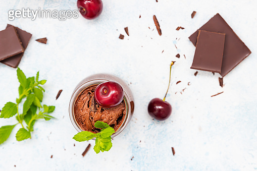Homemade dark chocolate mousse garnish with sweet cherry and mint and pieces of chocolate on light blue background.