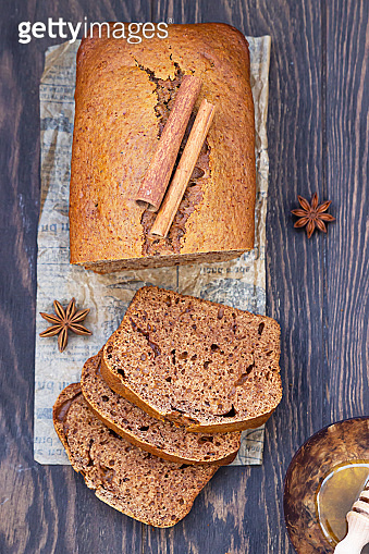 Gingerbread and honey loaf cake with cinnamon and anise on wooden background. Rustic style.