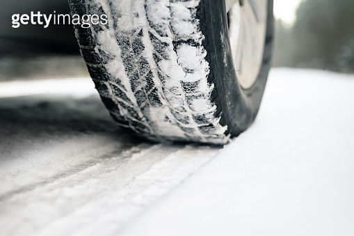 Closeup of car tires on a winter road covered with snow. Safe braking distance