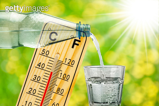 thermometer with high temperature, sunbeam and drinking glass with water